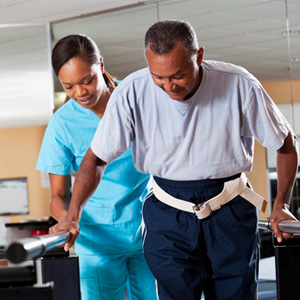 PT staff assting man with walking rehab