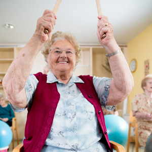 senior woman enjoying drumming exercise class