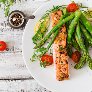 salmon with asparagus on white dinner plate