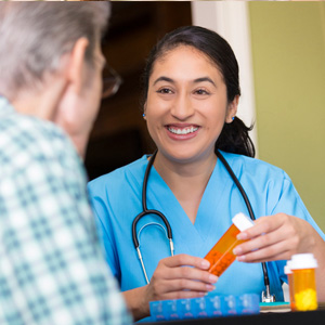 care staff assisting senior resident with prescriptions