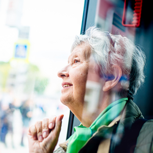senior looking out bus window on an excursion