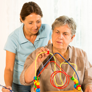 care staff assisting woman with occupational bead movement
