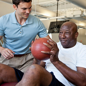 physical therapy staff assisting senior male with PT ball