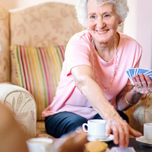 senior woman playing cards and drinking tea