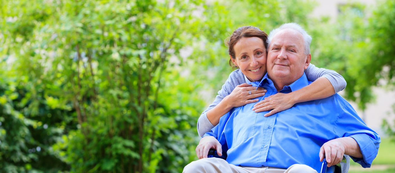 Caregiver with arms around shoulders of senior man in wheelchair